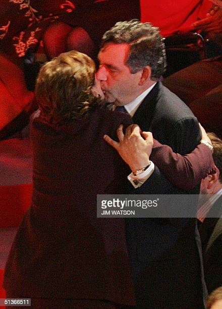 Britain's Chancellor of the Exchequer Gordon Brown kisses British Prime Minister Tony Blair's wife Cherie as she arrives to attend her husbands...