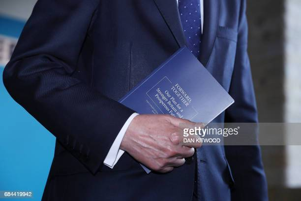 Britain's Chancellor of the Exchequer Philip Hammond holds a copy of the Conservative Party general election manifesto as he attends the launch event...