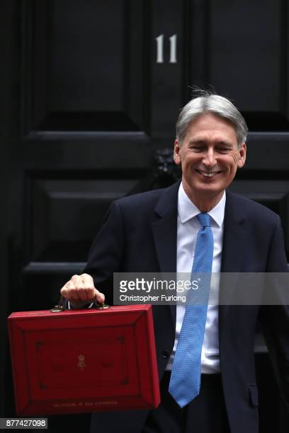 Britain's Chancellor of the Exchequer Philip Hammond holds the red case as he departs 11 Downing Street to deliver his budget to Parliament on...