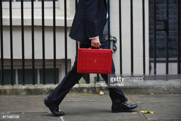 Britain's Chancellor of the Exchequer Philip Hammond holds the red case as he departs 11 Downing Street to deliver his Budget to Parliament London on...