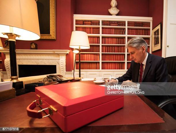 Britain's Chancellor of the Exchequer Philip Hammond poses putting finishing touches to his speech in his office in Downing Street central London on...