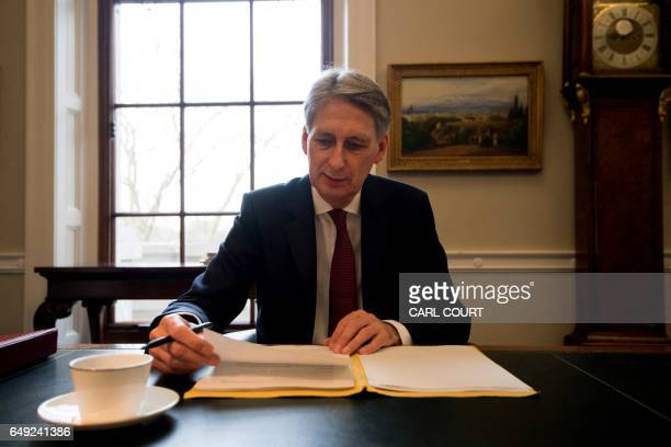 Britain's Chancellor of the Exchequer Philip Hammond prepares his speech in his office at the Treasury ahead of his 2017 budget annoucement on March...