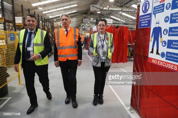 Britain's Chancellor of the Exchequer Philip Hammond walks with Eminox Managing Director Mark Runciman and Eminox Supply Manager Rachel Eldridge as...