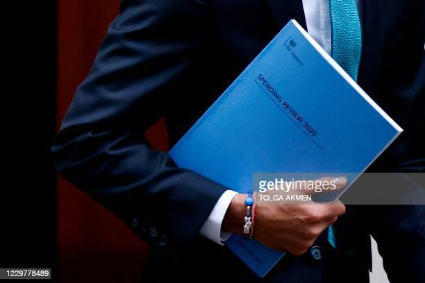 Britain's Chancellor of the Exchequer Rishi Sunak carries a copy of his Spending Review 2020 as he leaves 11 Downing Street in central London, on...