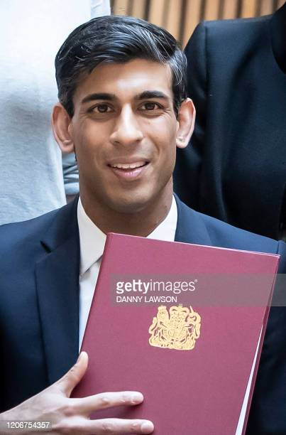 Britain's Chancellor of the Exchequer Rishi Sunak holds up the signed West Yorkshire Combined Authority devolution deal at the Nexus Building of the...