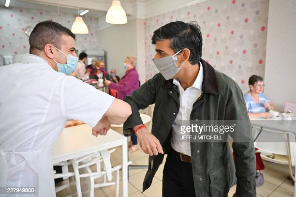 Britain's Chancellor of the Exchequer Rishi Sunak is greeted by a member of staff as he visits local businesses in Rothesay on the Isle of Bute,...