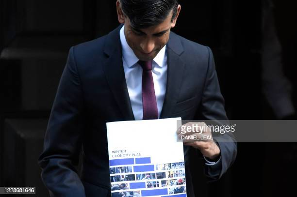 Britain's Chancellor of the Exchequer Rishi Sunak poses with his 'Winter Economy Plan' outside 11 Downing street in central London on September 24,...