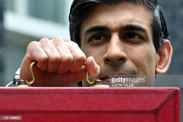 Britain's Chancellor of the Exchequer Rishi Sunak poses with the Budget Box as he leaves 11 Downing Street before presenting the government's annual...