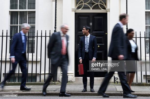 Britain's Chancellor of the Exchequer Rishi Sunak stands by holding the Budget Box as he and his Treasury team leave 11 Downing Street on March 11...