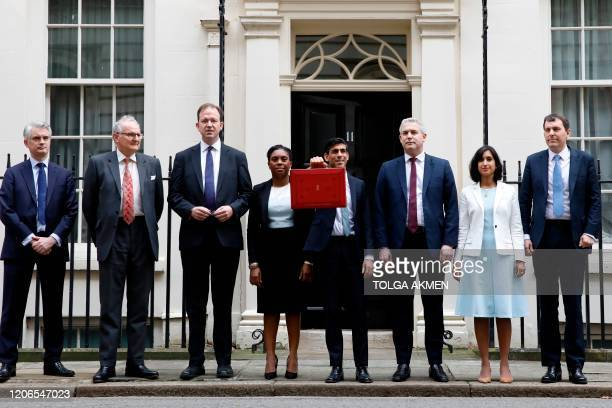 Britain's Chancellor of the Exchequer Rishi Sunak stands outside 11 Downing Street with his treasury team including Chief Secretary to the Treasury...
