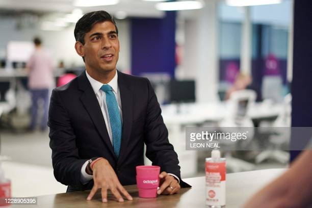 Britain's Chancellor of the Exchequer Rishi Sunak talks with members of staff during his visit to the headquarters of energy supplier Octopus Energy...