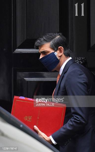 Britain's Chancellor of the Exchequer Rishi Sunak wearing a face mask or covering due to the COVID19 pandemic leaves from 11 Downing Street in London...