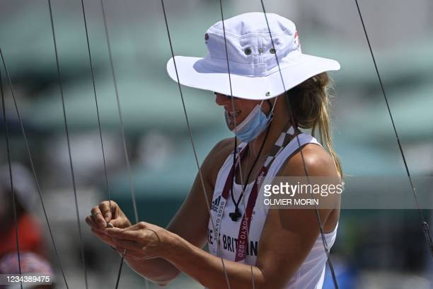 Britain's Charlotte Dobson folds ropes before the women's skiff 49er FX race during the Tokyo 2020 Olympic Games sailing competition at the Enoshima...