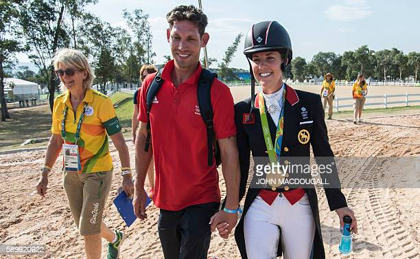 Britain's Charlotte Dujardin carrying her gold medal and her fiance Dean Golding walk hand in hand after the Equestrian's Dressage Grand Prix...