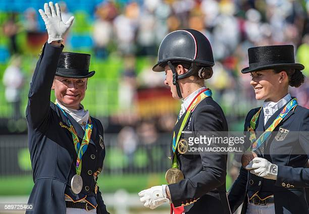 Britain's Charlotte Dujardin , Germany's Isabell Werth and Germany's Kristina Broring-Sprehe stand on the podium with their gold, silver and bronze...