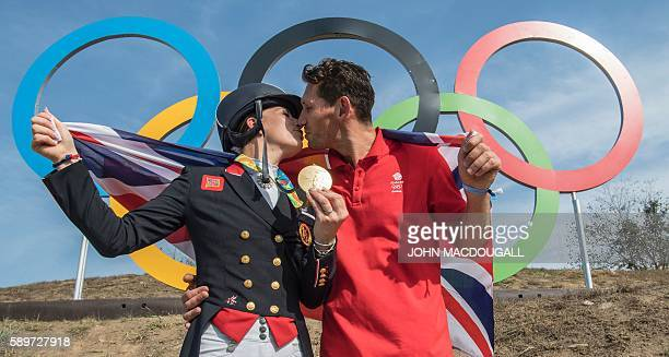 Britain's Charlotte Dujardin kisses her fiance Dean Golding as she poses with her gold medal in front of the Olympic rings after the Equestrian's...