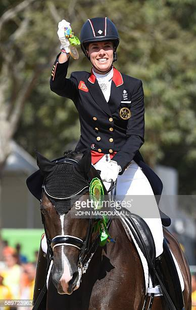 Britain's Charlotte Dujardin on Valegro shows her gold medal after a victory lap in the Equestrian's Dressage Grand Prix Freestyle event of the 2016...