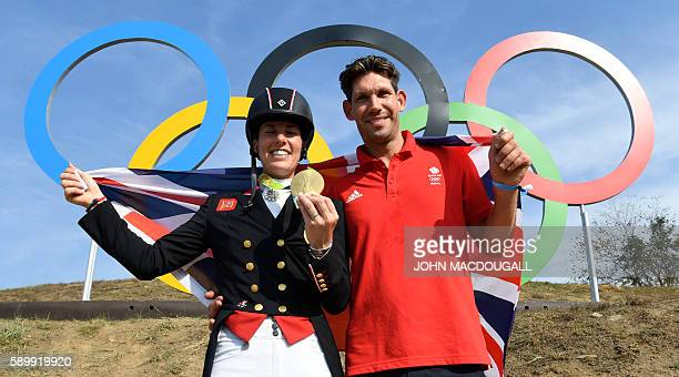 Britain's Charlotte Dujardin poses with her fiance Dean Golding and her gold medal in front of the Olympic rings after the Equestrian's Dressage...