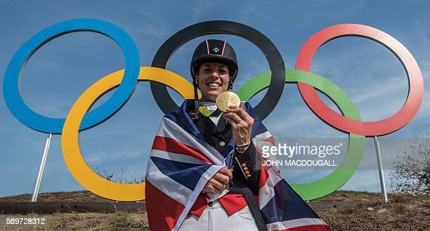 Britain's Charlotte Dujardin poses with her gold medal in front of the Olympic rings after the Equestrian's Dressage Grand Prix Freestyle event of...