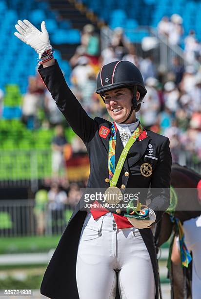 Britain's Charlotte Dujardin waves after receiving her gold medal during the Equestrian's Dressage Grand Prix Freestyle event victory ceremony of the...
