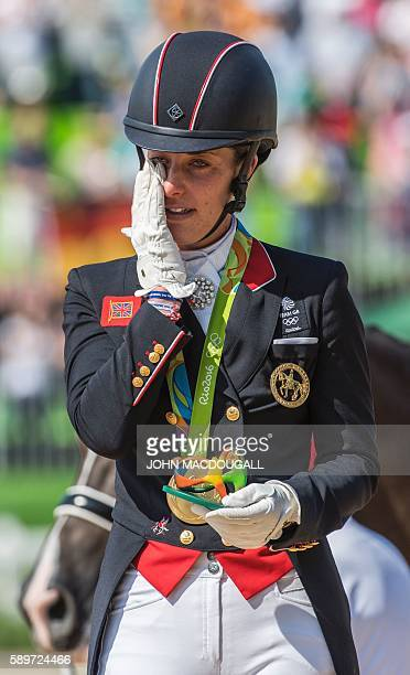 Britain's Charlotte Dujardin wipes a tear after receiving her gold medal during a victory ceremony after the Equestrian's Dressage Grand Prix...