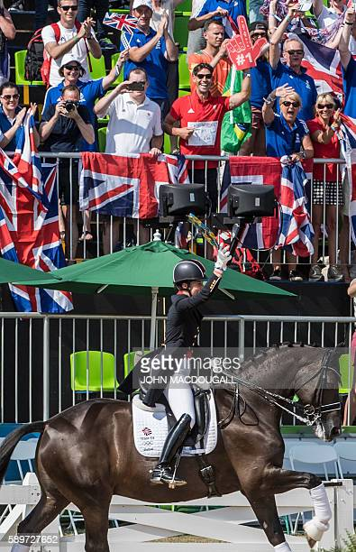 Britain's Charlotte Dujardin's fiance Dean Golding wears a sign on his shirt reading Can we get married now as she performs her victory lap after the...