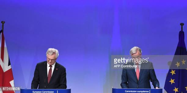 Britain's chief Brexit negotiator David Davis and EU's chief Brexit negotiator Michel Barnier read their notes as they address the media after a...