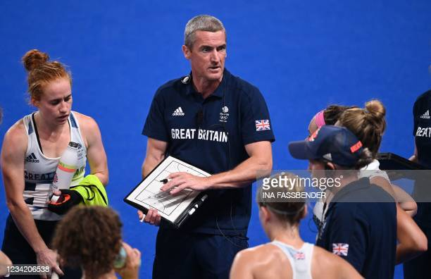 Britain's coach David Ralph talks to the players during the women's pool A match of the Tokyo 2020 Olympic Games field hockey competition against...