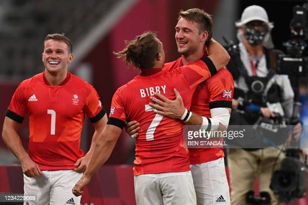 Britain's Dan Bibby celebrates winning with teammate Harry Glover and Max McFarland after the men's quarter-final rugby sevens match between Britain...
