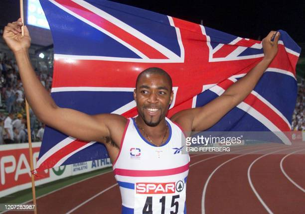 Britain's Darren Campbell celebrates with his country's flag after winning men's 100m final at the European Championships in Athletics in Budapest's...