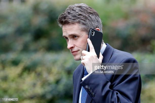 Britain's Defence Secretary Gavin Williamson speaks on a mobile phone as he arrives at 10 Downing Street in London on March 20 2019 Britain has asked...