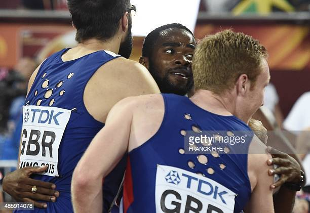 Britain's Delanno Williams hugs teammates Martyn Rooney and Jarryd Dunn during celebrations at the end of the final of the men's 4x400 metres...