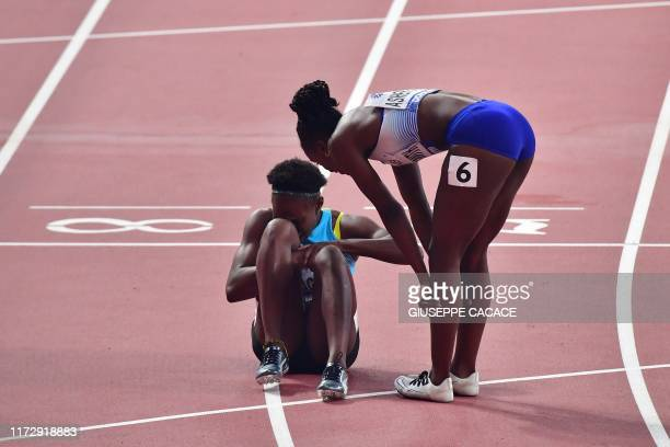 Britain's Dina AsherSmith helps Bahamas' Anthonique Strachan after picking up an injury while competing in the Women's 200m semifinal at the 2019...