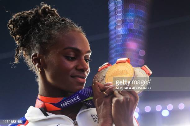 Britain's Dina AsherSmith poses with her gold medal for the Women's 200m silver medal for the Women's 100m and silver medal for the Women's 4x100m...
