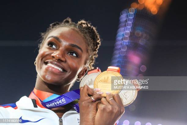 TOPSHOT Britain's Dina AsherSmith poses with her gold medal for the Women's 200m silver medal for the Women's 100m and silver medal for the Women's...