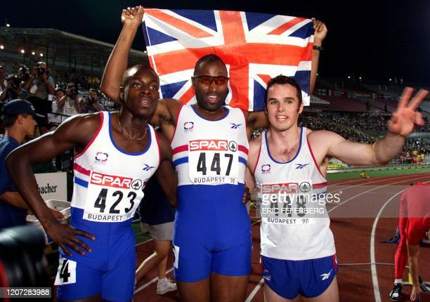 Britain's Doug Walker European champion over 200m second placed Doug Turner and third placed Julian Golding celebrate with their country's flag after...