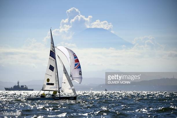 Britain's Eilidh Mcintyre and Hannah Mills compete in front of Mount Fuji in the women's two-person dinghy 470 medal race during the Tokyo 2020...