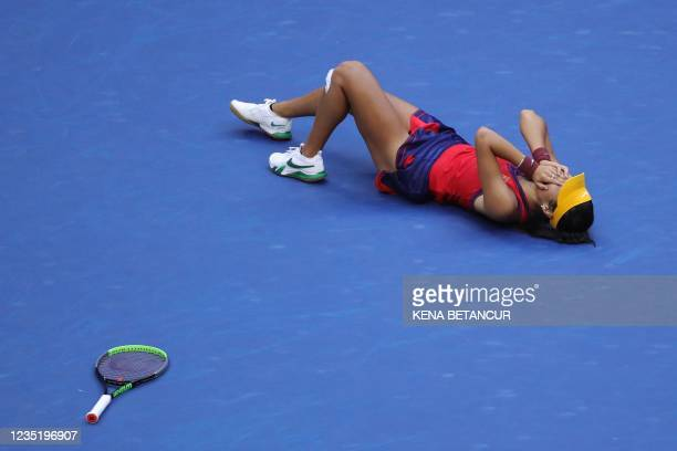 Britain's Emma Raducanu lies on the court as she reacts after winning her 2021 US Open Tennis tournament women's singles final match against Canada's...