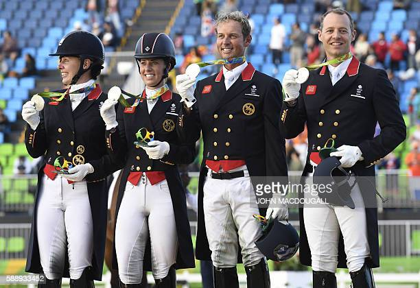 Britain's Fiona Bigwood, Britain's Charlotte Dujardin, Britain's Carl Hester and Britain's Spencer Wilton salute the crowd on the podium after...
