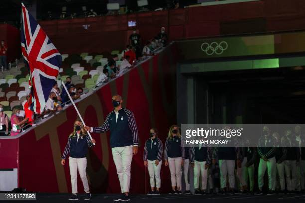 Britain's flag bearers Hannah Mills and Mohamed Sbihi lead the delegation during the Tokyo 2020 Olympic Games opening ceremony's parade of athletes,...