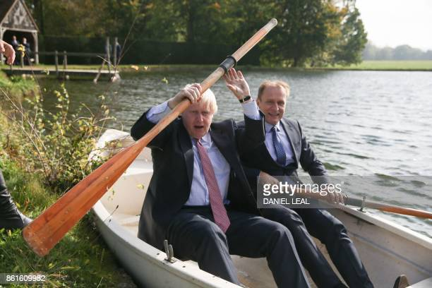 Britain's Foreign Secretary Boris Johnson boards a row boat with Czech Republic's Deputy Foreign Minister Ivo Sramek on a boating lake in the grounds...