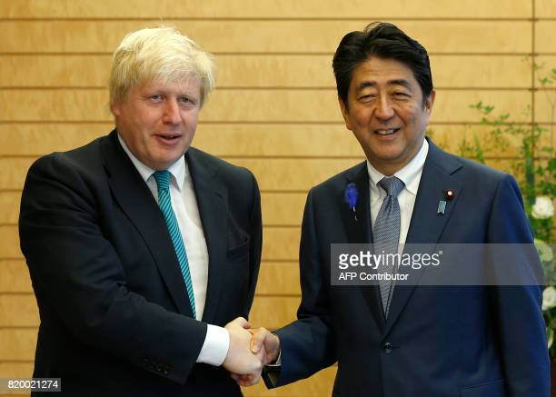 Britain's Foreign Secretary Boris Johnson shakes hands with Japan's Prime Minister Shinzo Abe at Abe's official residence in Tokyo on July 21 2017...