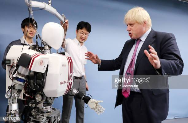 Britain's Foreign Secretary Boris Johnson speaks with Associate Professor Kenji Hashimoto as they look at the bipedal humanoid robot Wabian2 at the...