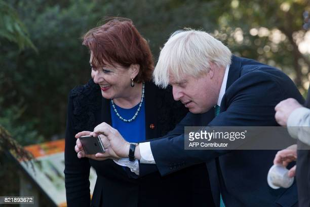 Britain's Foreign Secretary Boris Johnson takes a photo of a South Island takahe as New Zealand's Conservation Minister Maggie Barry looks on during...