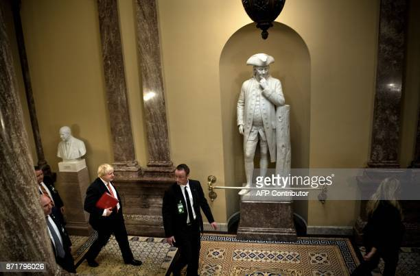 Britain's Foreign Secretary Boris Johnson walks past a statue of Benjamin Franklin while visiting US lawmakers about Iran on Capitol Hill November 8...