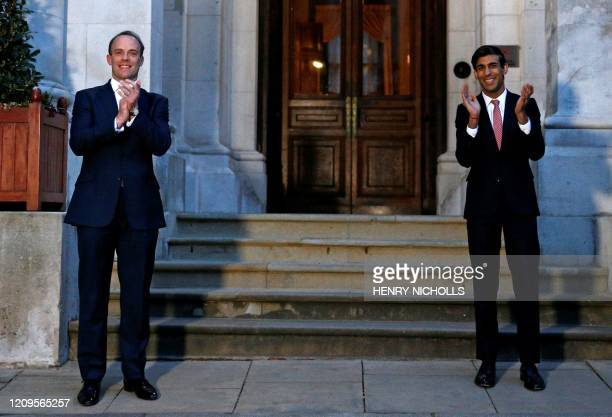 TOPSHOT Britain's Foreign Secretary Dominic Raab and Britain's Chancellor of the Exchequer Rishi Sunak take part in a national clap for carers to...