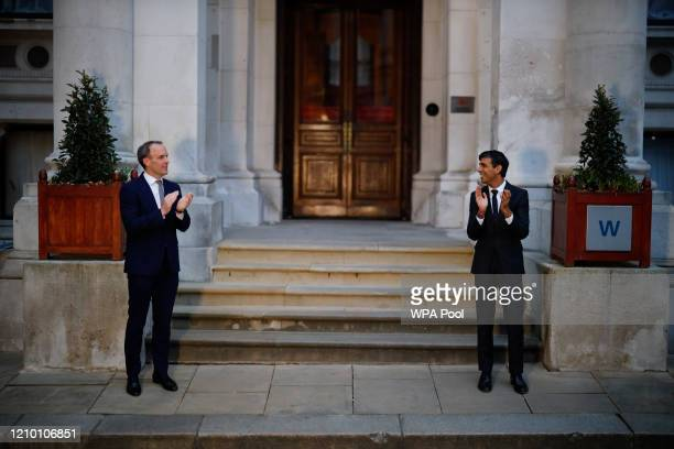 Britain's Foreign Secretary Dominic Raab and Britain's Chancellor of the Exchequer Rishi Sunak take part in a national clap for carers to show thanks...