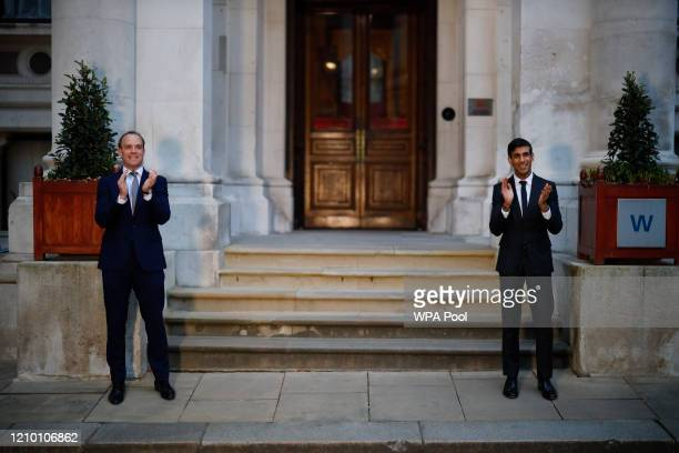 Britain's Foreign Secretary Dominic Raab and Britain's Chancellor of the Exchequer Rishi Sunak takes part in a national clap for carers to show...