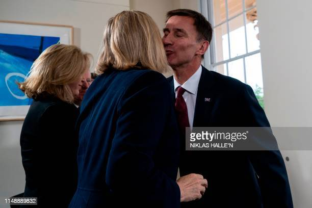 Britain's Foreign Secretary Jeremy Hunt's is applauded by Britain's Defence Secretary and Minister for Women and Equalities Penny Mordaunt and...