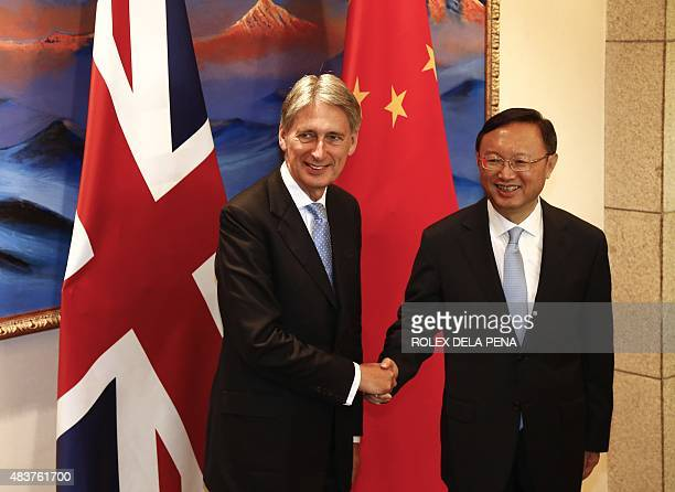 Britain's Foreign Secretary Philip Hammond shakes hands with Chinese State Councillor Yang Jiechi as they face the media during the ChinaUK Strategic...